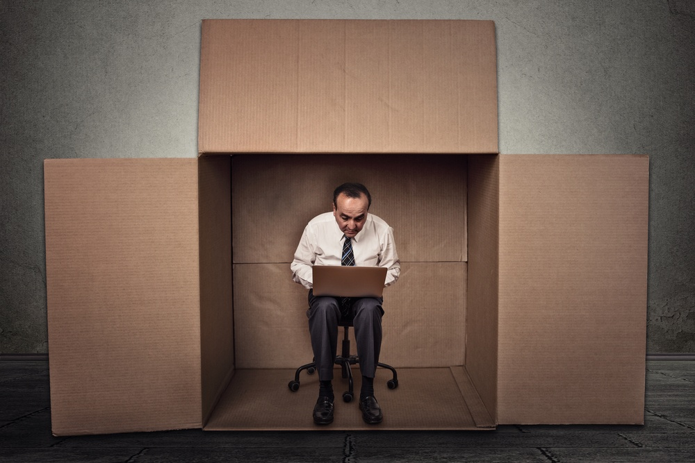 Limitations poor communication of corporate life. Portrait corporate middle aged man working on laptop sitting on chair inside carton box in empty office room