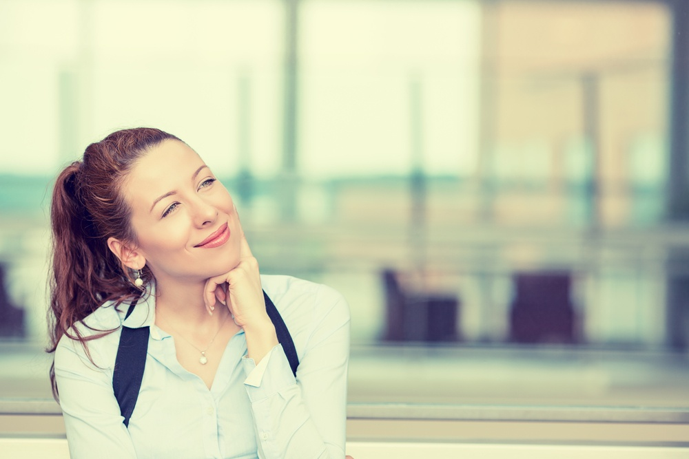Portrait happy young woman thinking dreaming has many ideas looking up isolated office windows background. Positive human face expression emotion feeling reaction. Decision making process concept
