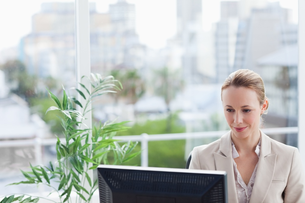 Woman working on a computer with city view in background